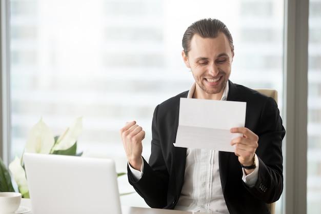 幸せなビジネスマンは良いビジネスニュースの受信を祝う