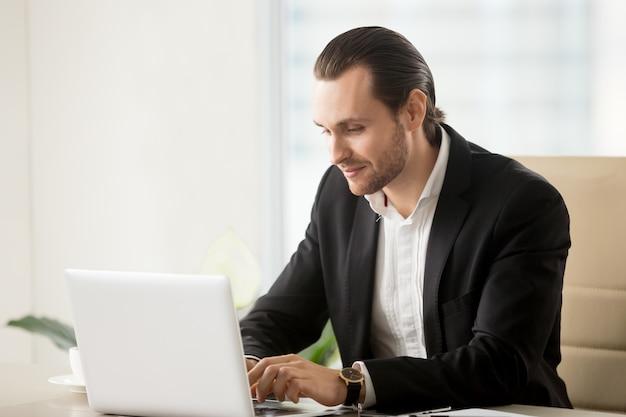 実業家のオフィスの机でノートパソコンに入力します。