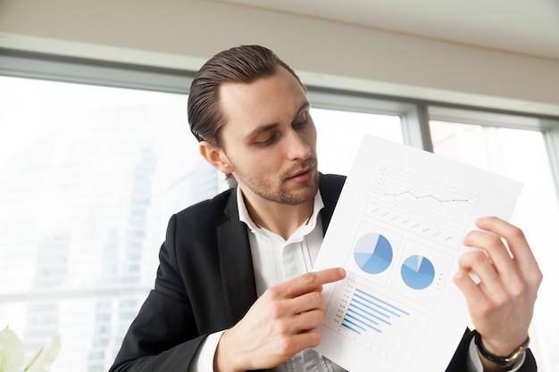 ビジネスマンはインフォグラフィックとドキュメントを保持します