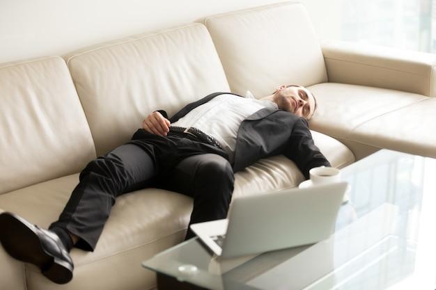 Утомленный бизнесмен спать на софе в офисе