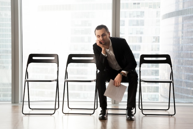 待合室に座っているスーツで退屈な若い男。