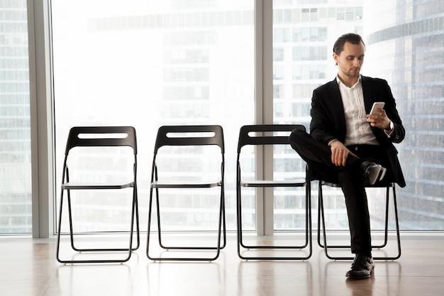 インタビューに彼の順番を待っている携帯電話を持つ男