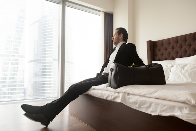 Расслабленный бизнесмен сидя на кровати кроме сумки багажа.
