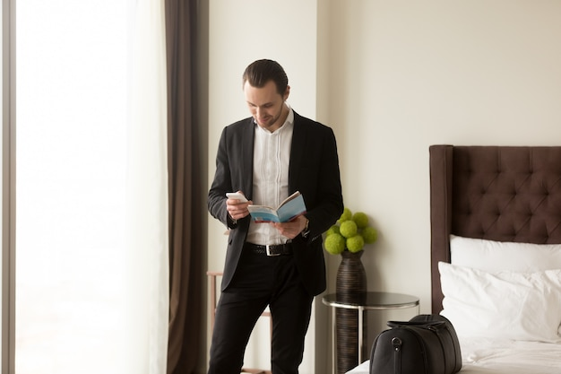 ビジネスマンはガイドパンフレットを保持します