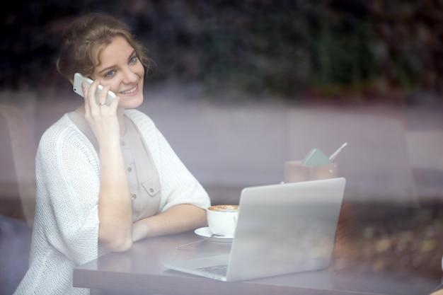 コーヒーショップで電話で話す笑顔実業家