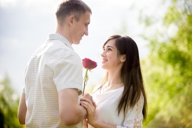 Романтический парень дает цветок к его улыбающейся девушке