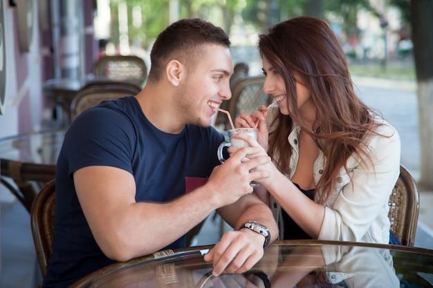 ミルクセーキを共有する若いカップル