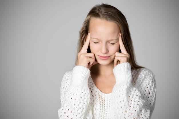 Концентрированный девушка с пальцами на лбу