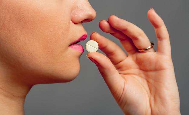 Женщина принимает таблетку на сером