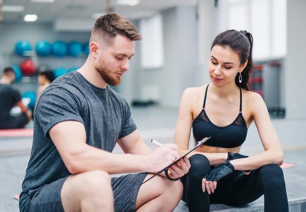 背景をぼかした写真のかわいい女の子のためのクリップボードの特別なトレーニングに書く筋肉の男性インストラクター。