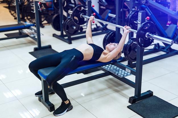プロのスポーティな女性は、ジムのシミュレーターで筋肉の腕と胸を構築します。