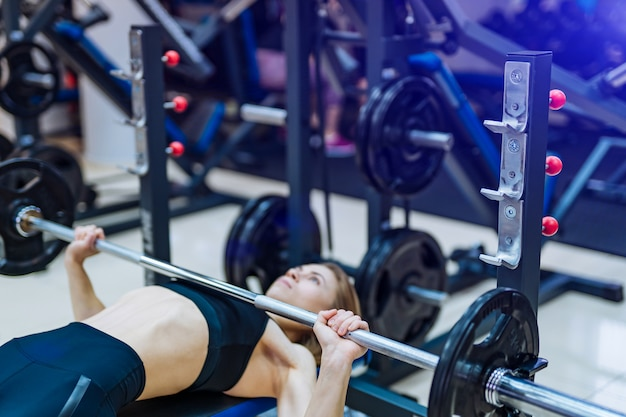 Спортивная (ый) девушка поднимает штангу, лежа на скамейке на тренажере в тренажерном зале.
