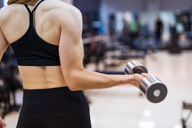 フィットネスクラブでダンベルで腕と背中の筋肉をポンピングスポーツウェアに戻って立っているボディービルダーの女性。