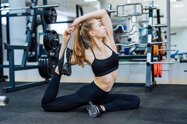 フィットネスセンターで近代的なシミュレーターの近くの床で演習を行う魅力的なスポーツウーマンの側面図。