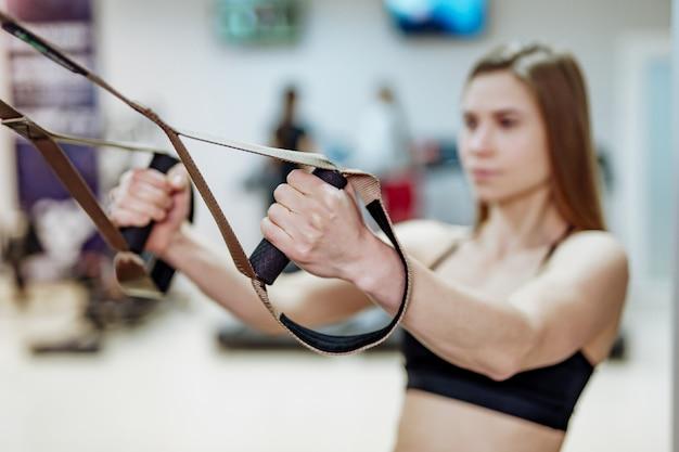 細い女の子は、ジムでのサスペンショントレーニングのために、フィットネスストラップを手に持っています。
