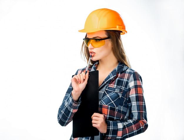 ヘルメットと安全メガネで深刻な若い女性の肖像画はペンで彼女の唇に触れると分離を考えて。