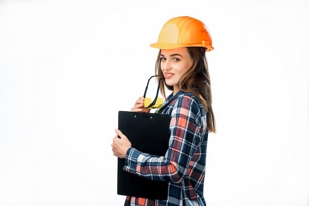 ハード帽子と白で隔離される彼女の唇に触れる黄色のメガネと美しい労働者モデルの肖像