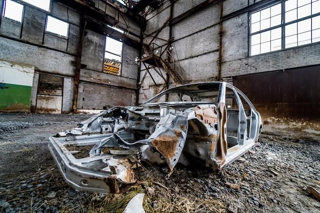 Покинутая в пустом здании старая ржавая кабина легкового автомобиля.
