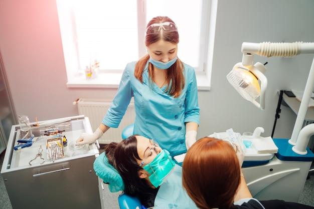 医師口科医の女性と彼女の女性アシスタントは、クリニックで患者と働いています。
