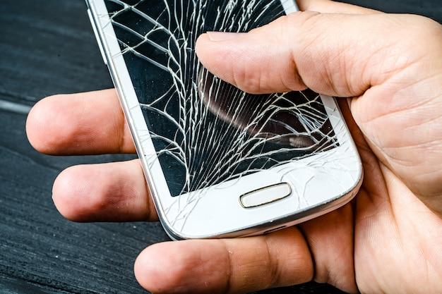 Рука человека держа мобильный телефон с сломленным экраном над темнотой. смартфон с разбитым стеклом сенсорного экрана в руке человека. крупный план