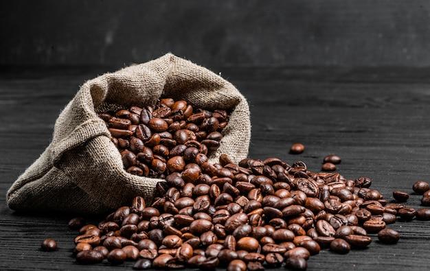 Органические семена кофе разбрасывают из мешка по темной деревянной поверхности. свежие кофейные зерна около русого изолированного мешка. крупный план