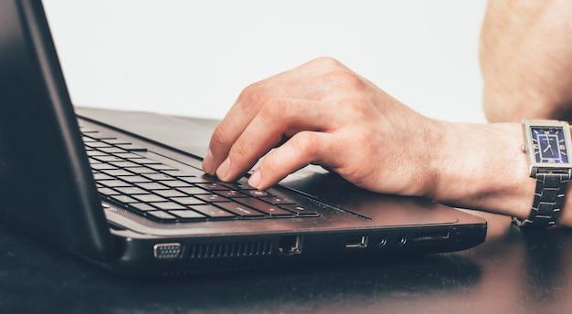 オフィスの仕事でキーボードでテキストを入力する腕時計を持つ男の手