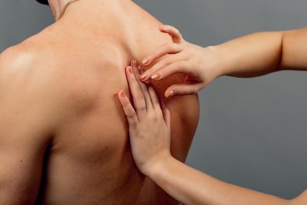 クローズアップ裸の男の体と女性の手が戻って確認します。医師の手は灰色の背中の痛みを持つ男を調べます。
