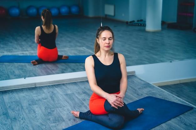 ジムの鏡に戻って座って目を閉じてヨガの練習の若い女性。フィットネスクラブで運動ヨガのポーズでリラックスした女性。