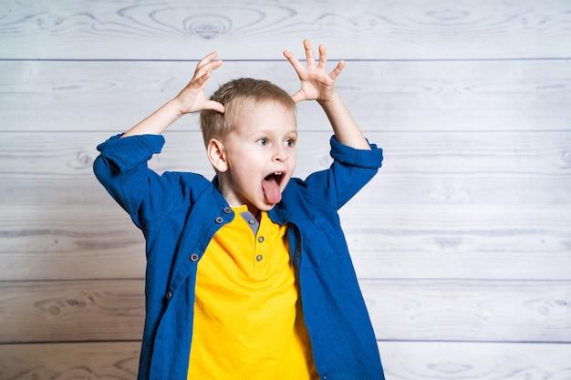 Маленький мальчик с его руки над головой показывает язык. забавный малыш в желтой футболке и синей рубашке делает глупое лицо, глядя в будущее