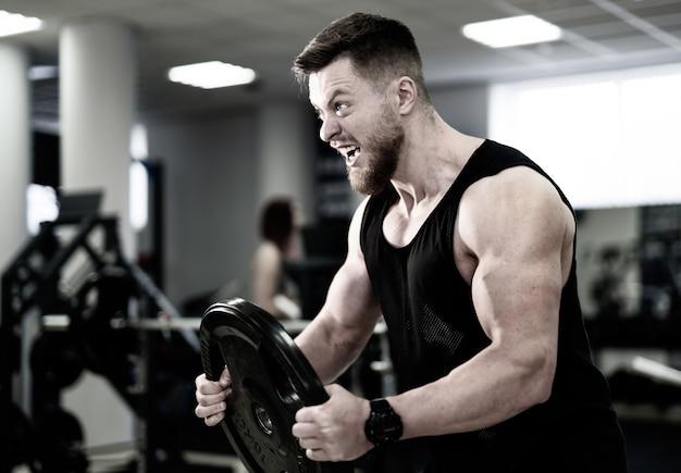 ジムでディスクの重みを保持している大きな筋肉を持つ健康な若者の側面図。トレーニング中に力で重いディスクを持ち上げるボディービルダー。フィットネス、スポーツ、トレーニング、動機、ライフスタイルのコンセプト。