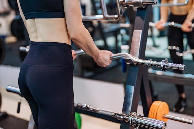 鏡の前でシミュレーターの近くに立っている女性の体の背面図。スリムな女性は、ジムでトレーニングをしています。閉じる。