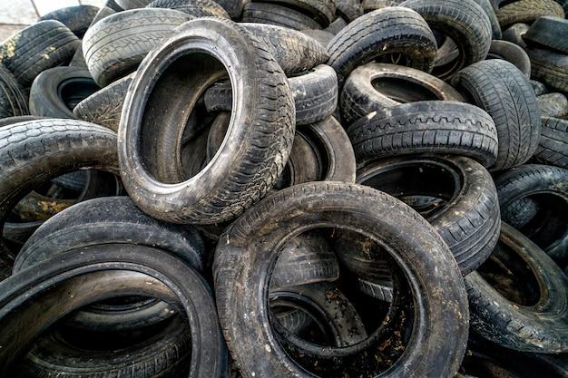 Куча мусора готова к утилизации. старые изношенные шины на заброшенной свалке