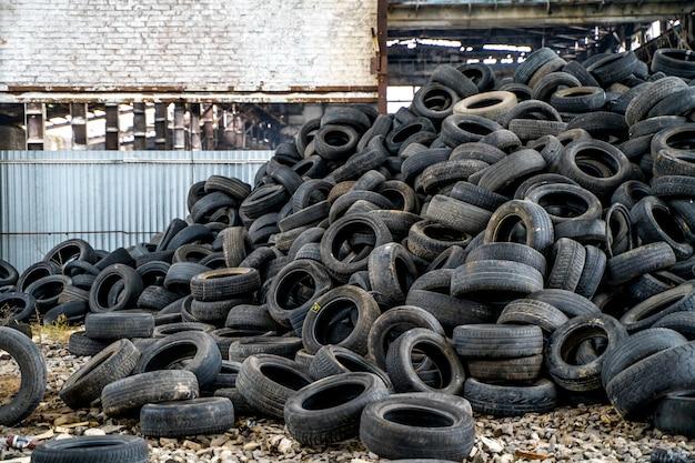 古いゴム製タイヤが捨てられました。廃品の中古車のタイヤのマウンドのビュー