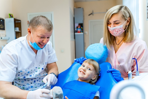 歯科医のキャビネットの少女。歯科医のチームが働いています。