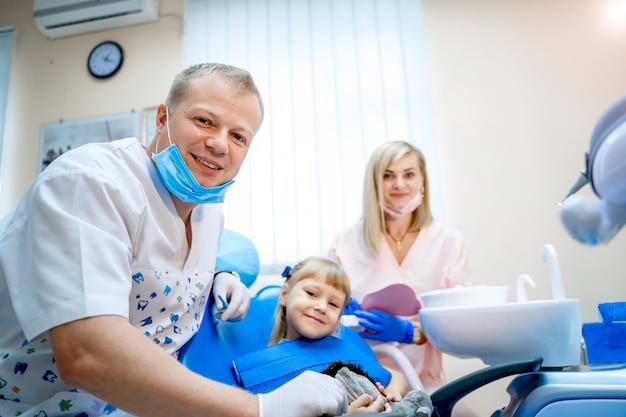 Маленькая девочка в кабинете стоматолога. стоматолог команды работает.