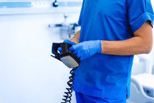 手の除細動器。青い医療服。応急処置。外部ペーサーアナライザー、除細動器を使用して命を救います。