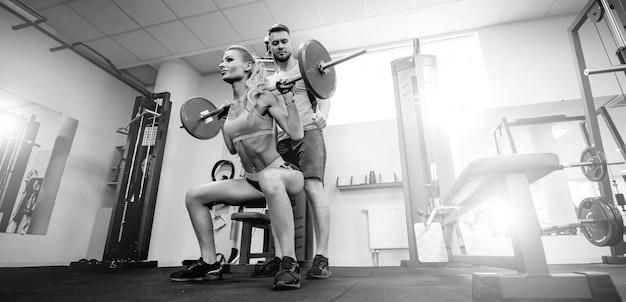 スポーツ、ボディービル、ライフスタイル、人々のコンセプト-若い男性と女性のバーベルの筋肉がうごめくとジムでショルダープレススクワットを作る。ひざまずく姿勢、スクワットジョギングをサポート。