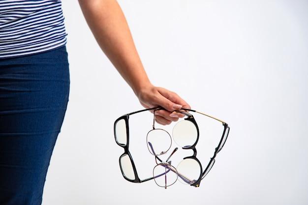 眼鏡のクローズアップ。女性の手は黒いフレームの眼鏡を保持しています。