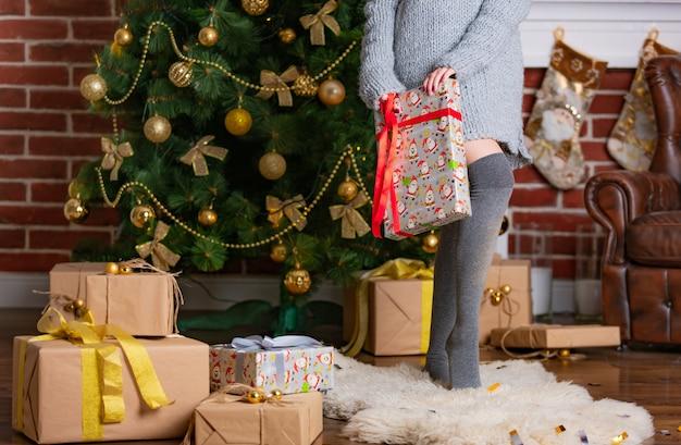 Женщина в сером платье стоит на цыпочках в гетрах на меховом коврике и держит в руке подарок с красной лентой.