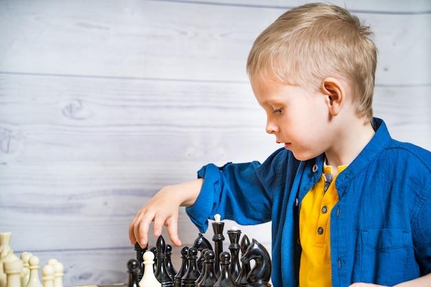 Мальчик играет в шахматы. милый маленький ребенок играет логику и мозг развивающую настольную игру.