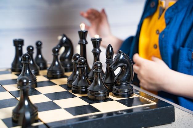 かわいい金髪の少年がチェスをしている間彼の動きをしています。ロジック開発ボードゲーム。