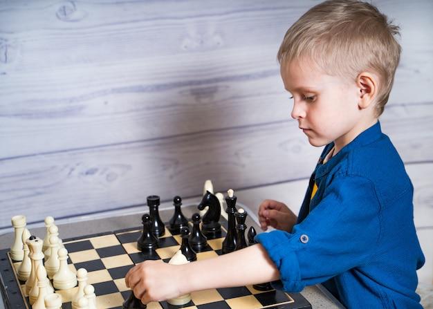 Милый маленький белокурый мальчик делает его движение во время игры в шахматы. развивающая логика настольная игра.