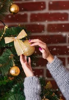 女性の手は、冬の部屋の雪の背景に蝶結びで金色のボールでクリスマスツリーを飾ります。閉じる