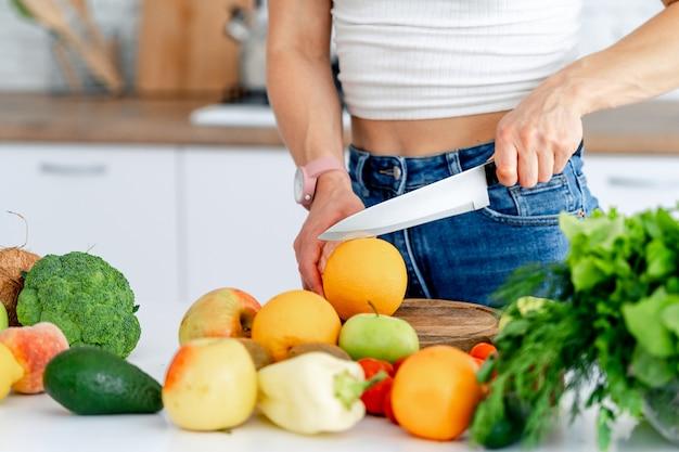 キッチンで健康食品を準備する女性。オレンジをスライスします。健康食品のコンセプトです。ビーガンとベジタリアン。閉じる。果物と野菜。
