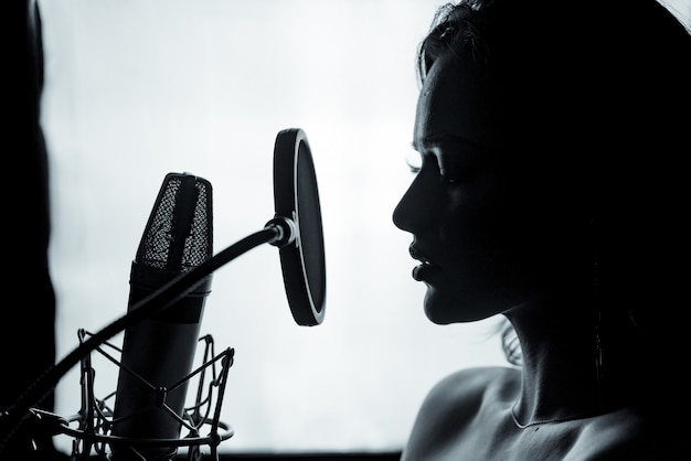 Молодая женщина с микрофоном в студии звукозаписи. профессиональная запись вокала. красивая девушка певица. портрет. крупный план.