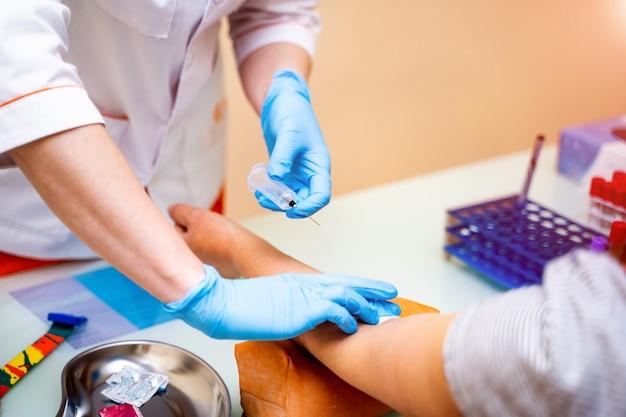 患者の診断と治療のための看護師の手の血液サンプル分析のクローズアップ。自動機による血液生化学診断。閉じる。