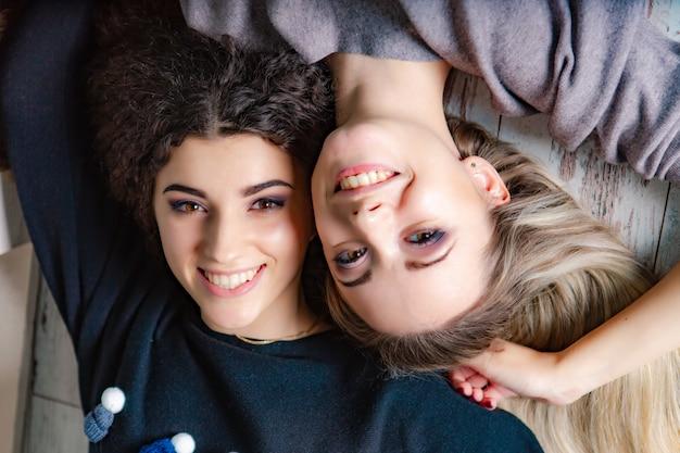 暖かいセーターを着た美しい姉妹がスタジオの床に横たわり、笑顔になります。閉じる