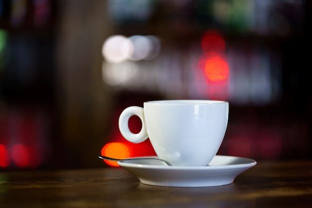 受け皿とスプーン付きの白いマグカップは、レストランの木製テーブルの上にあります。