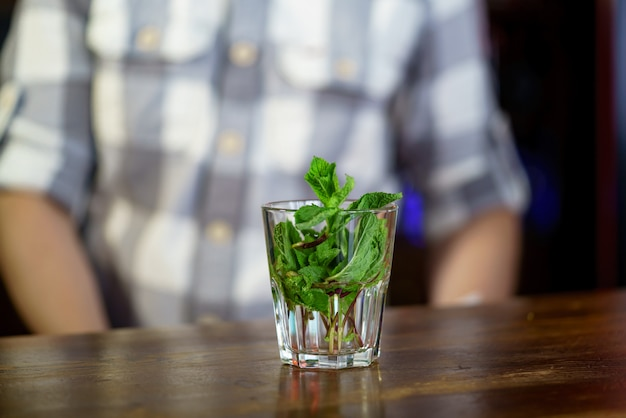 香り高いミントの枝で満たされたガラスは、格子縞のシャツを着た男の木製テーブルの上に立つ。