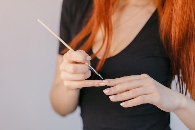 Женщина лакирует ноготь с помощью тонкой кисти на пальцах.